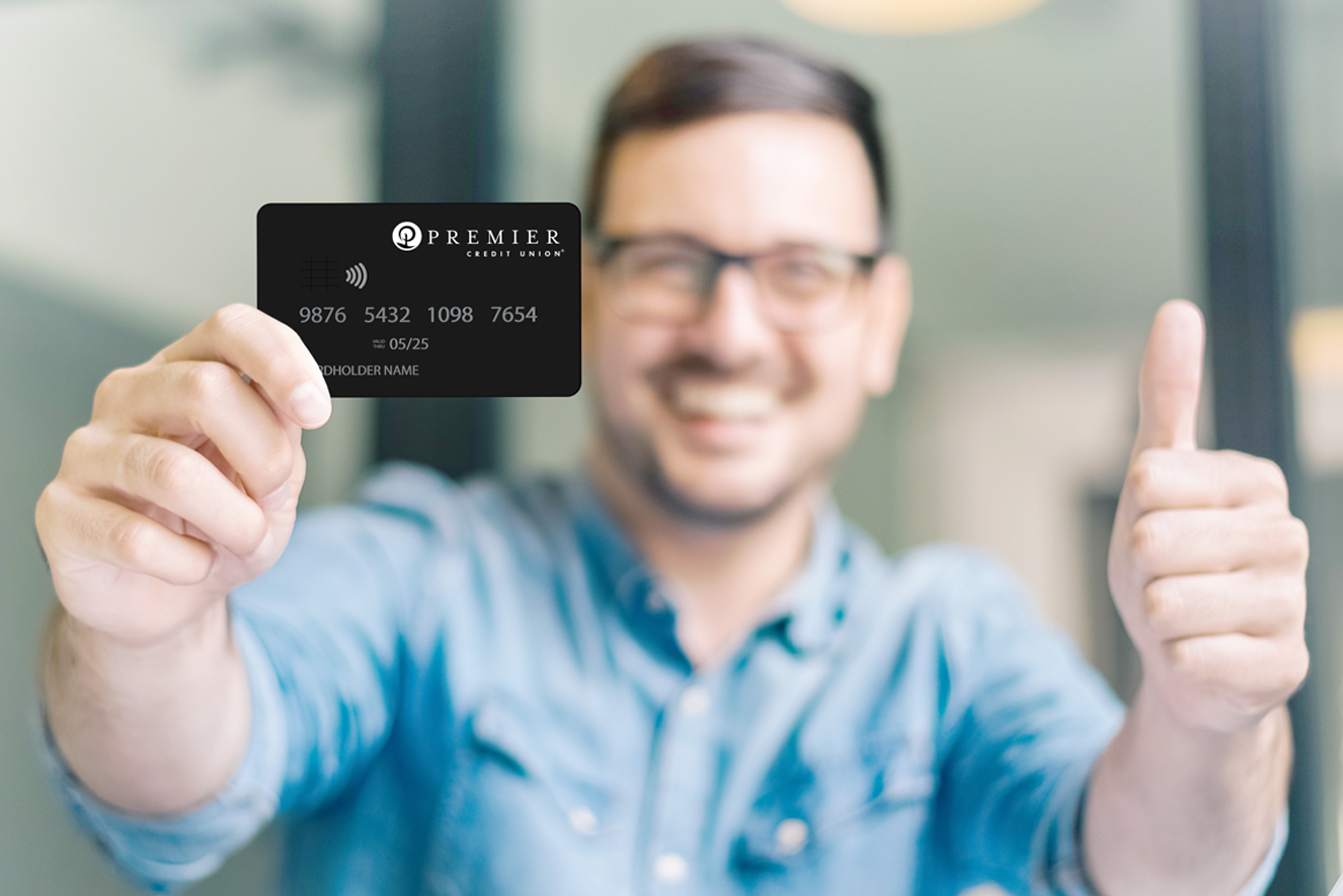 Man holding a PCU credit card with a thumbs up